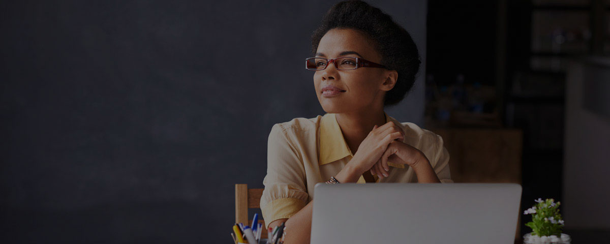 Photograph of a woman with short black hair and glasses sitting in front of a computer while looking off into the distance.