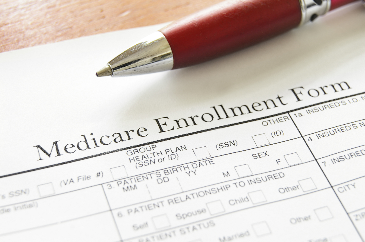 Close-up photograph of a thick maroon pen sitting over a Medicare Enrollment form.