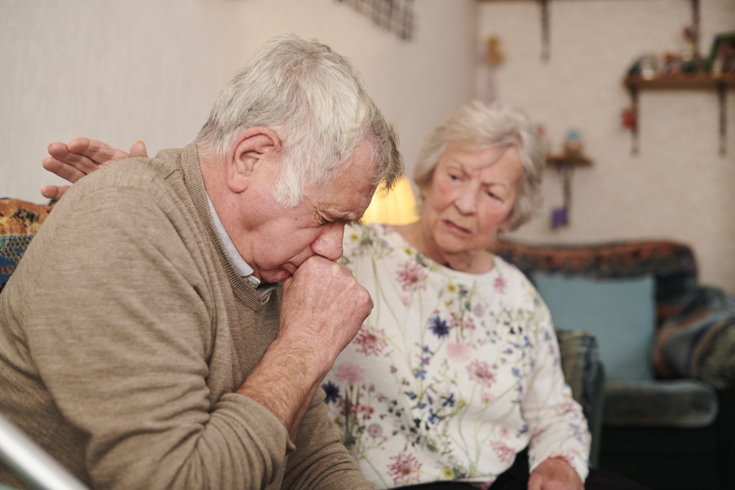 Photograph of an older couple in a living room. The man is coughing as the woman looks at him with concern.