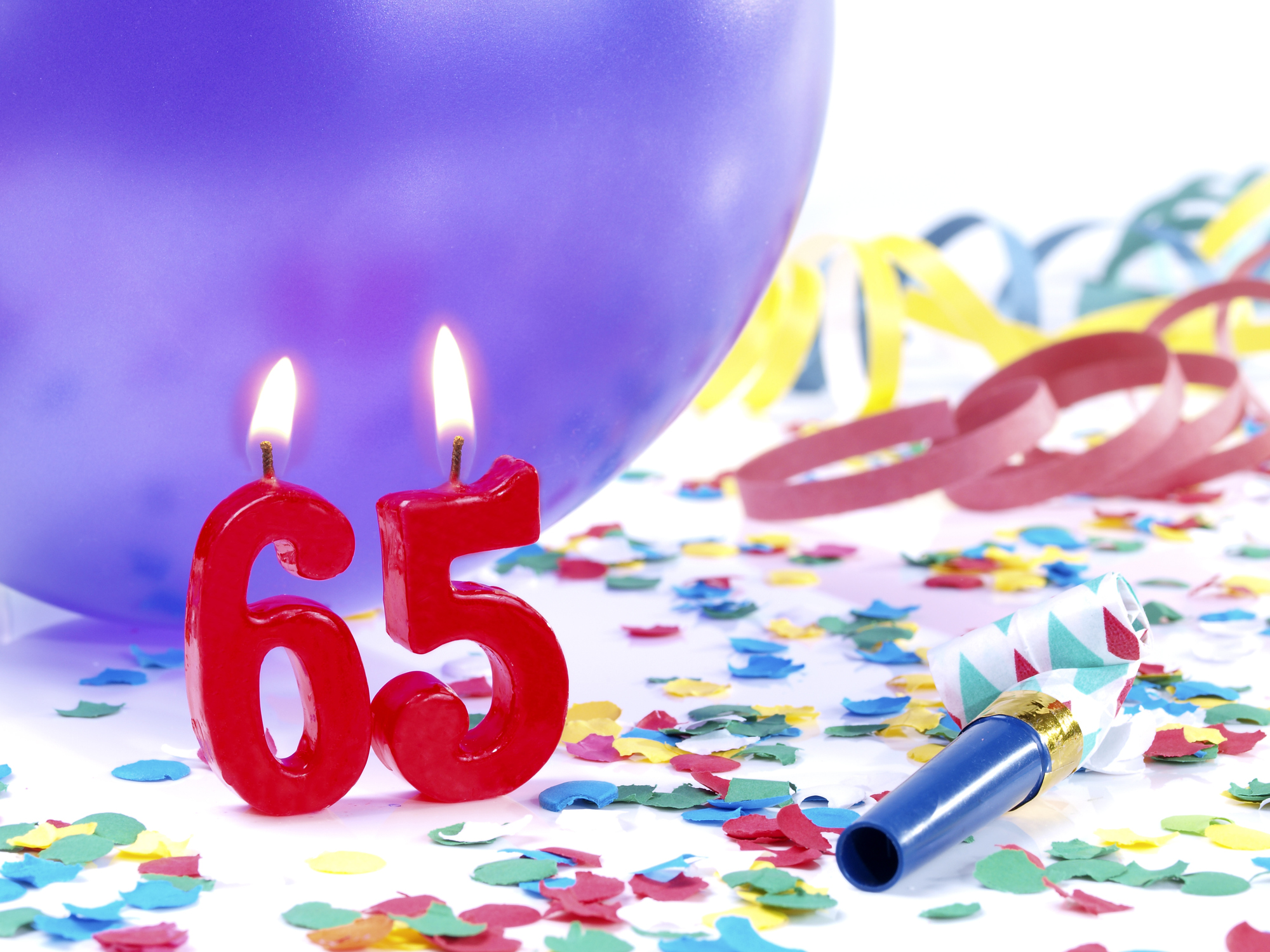 Two birthday candles that are lit surrounded by confetti and a purple balloon. The candles are in the shape of a 6 and a 5.