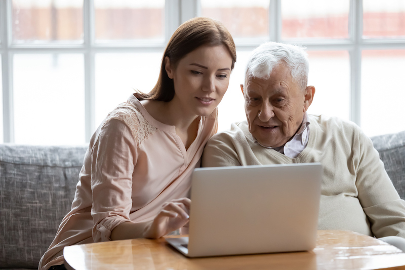 daughter with elderly father on computer