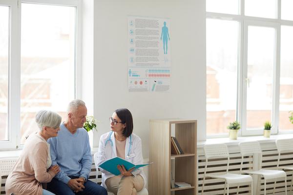 female doctor registering elderly couple for medicare