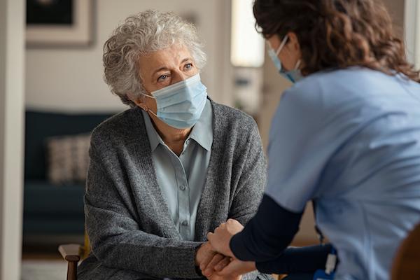 elderly woman wearing mask with nurse