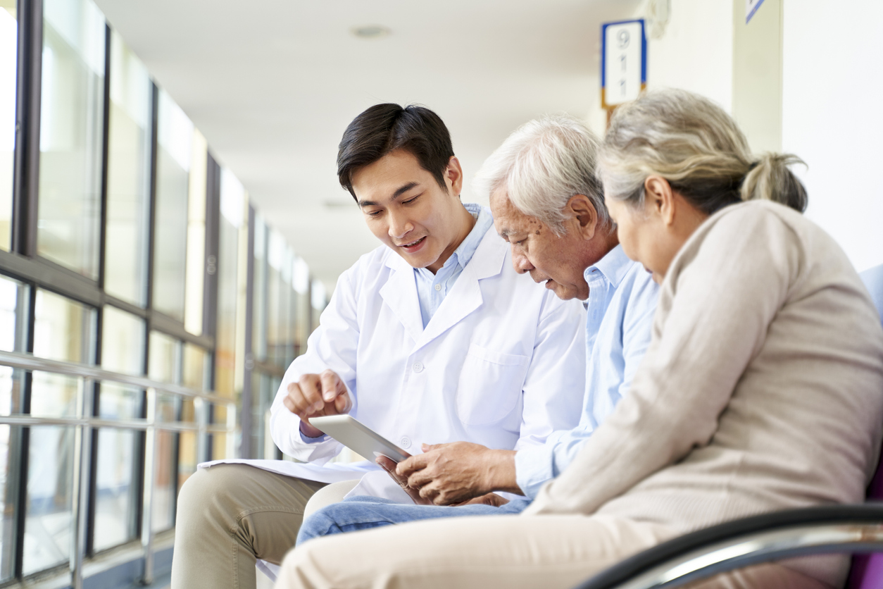 doctor discussing medicare with elderly patients