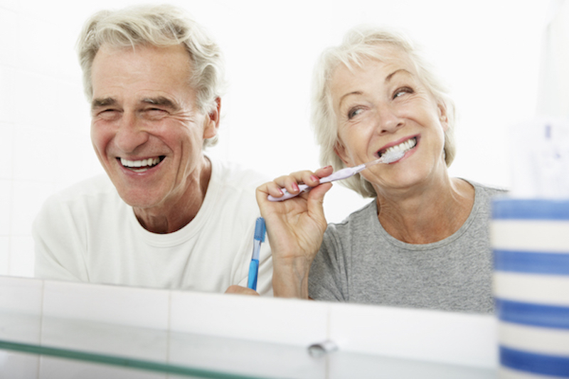 senior couple brushing teeth