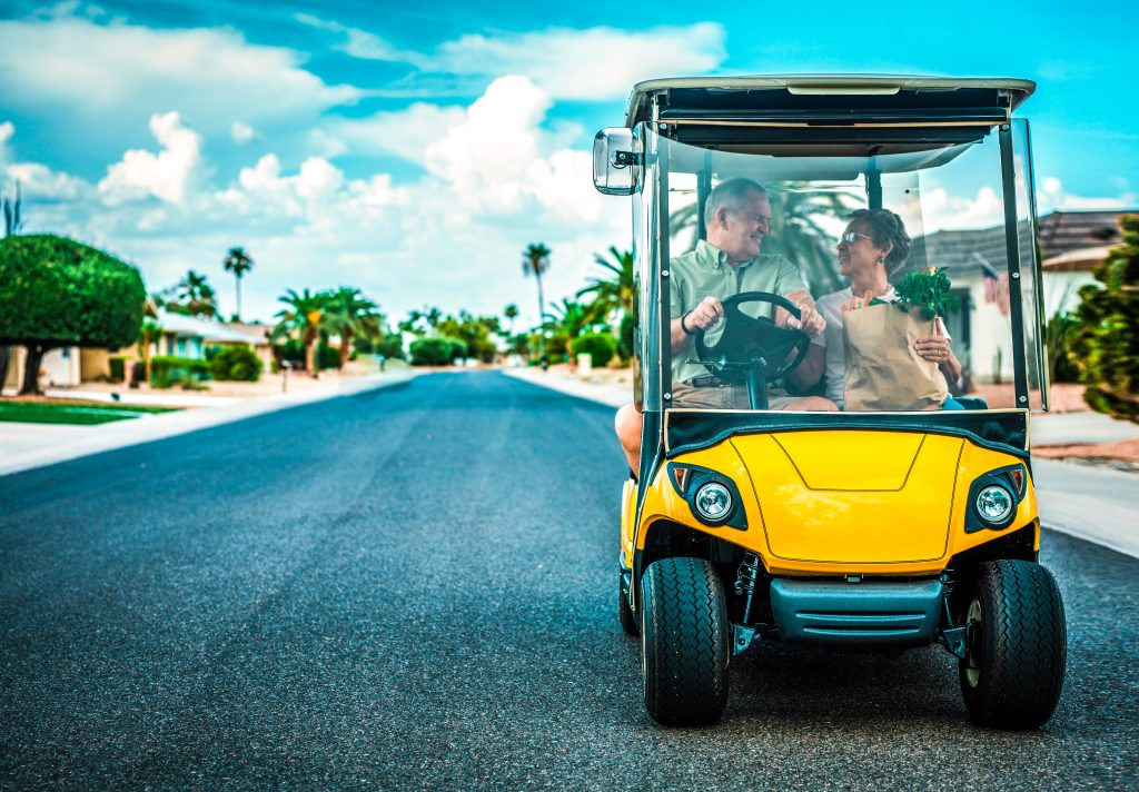 Senior Couple in Golf Cart with Grocery Bag